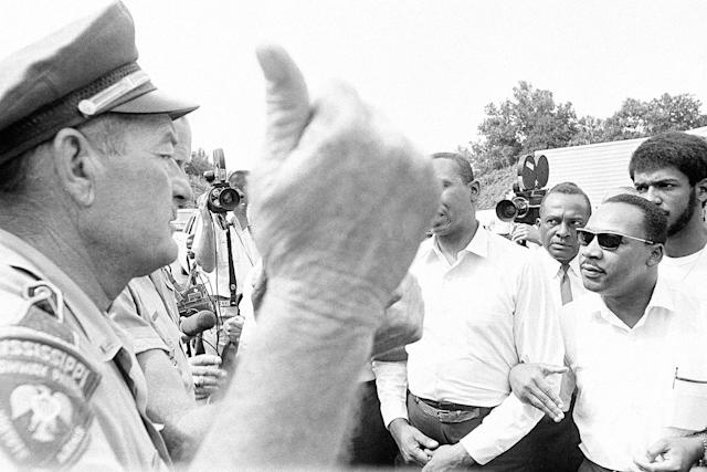 <p>A Mississippi Highway Patrolman gestures with his thumb as he orders the Rev. Dr. Martin Luther King, right, and other marchers from the pavement of U.S. 51 near Hernando on June 7, 1966. (AP Photo) </p>