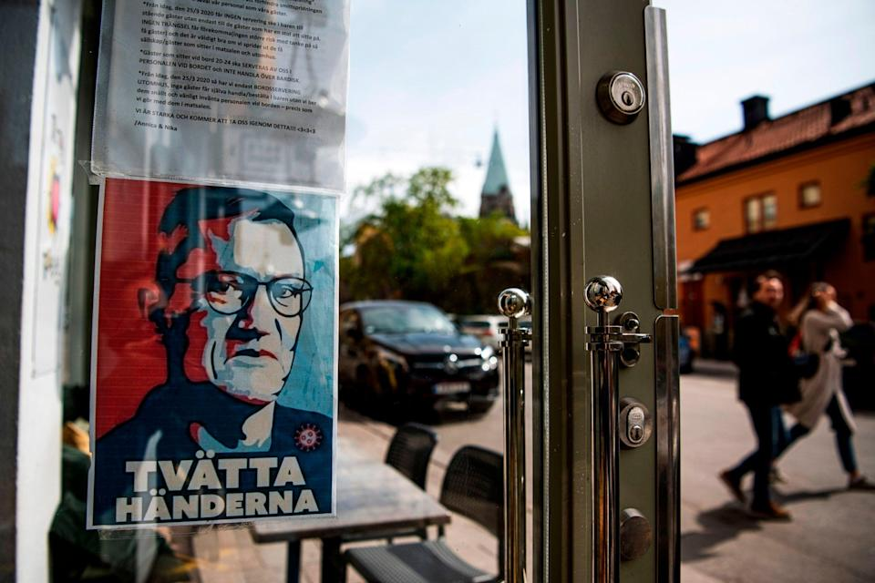 A portrait of Anders Tegnell hangs in the entrance to a restaurant to instruct people to wash their hands in Sodermalm (AFP via Getty Images)
