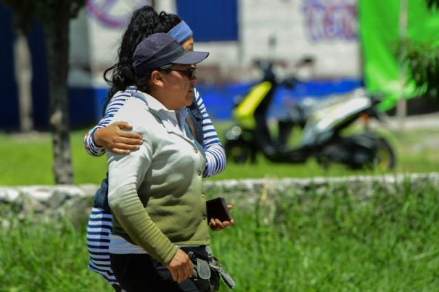 <p>Women walk away from the site of a series of explosions at fireworks warehouses in Tultepec, central Mexico, on July 5, 2018. – At least 17 people were killed, including rescue workers who died saving others' lives, officials said. The initial explosion occurred around 9:30 am (1430 GMT), then spread to other warehouses just as police and firefighters began attending to the first victims. (Photo: Pedro Pardo/AFP/Getty Images) </p>