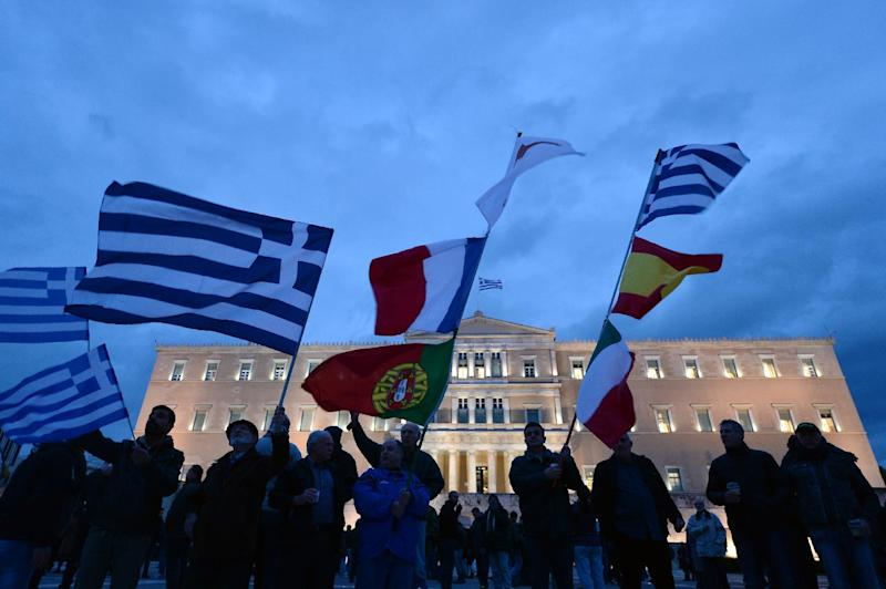 People hold the flags of Greece and other EU countries in front of the Greek parliament, during a pro-government demonstration in Athens, on February 16, 2015 (AFP Photo/Louisa Gouliamaki)