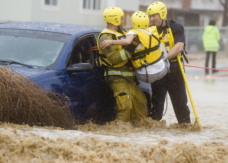 San Bernardino County Firefighters Jay Hausman, left, and Ryan Beckers, right, pull a victim from a car caught in swift water at Hughes and Avalon Road in Victorville, Calif., Monday, Dec. 20, 2010. (AP Photo/Daily Press, James Quigg)