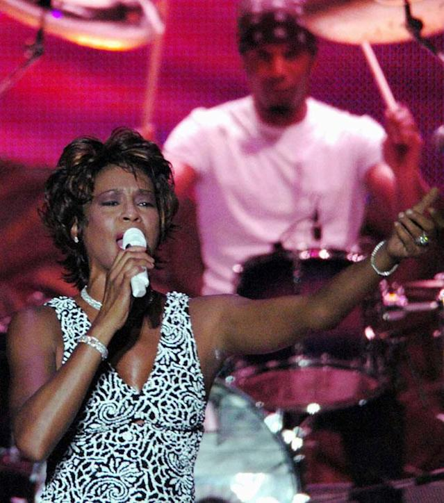 American pop singer Whitney Houston sings during a concert in the Olympic Sports Center in Beijing, capital of China, Sunday, July 25, 2004. The concert, part of Houston's China tour, drew more than 20,000 audience. (AP Photo/Xinhua, Wang Jianhua)