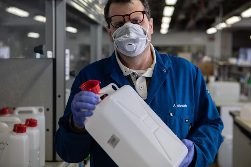 MILAN, ITALY - MARCH 19: Professor Alessandro Volonterio, wearing gloves and a protective face mask, shakes a jerrycan as he works inside the laboratory of Chemistry, Materials and Chemical Engineering 'Giulio Natta' at Politecnico di Milano on March 19, 2020 in Milan, Italy. Following the national shortage of hand sanitiser products due to the novel Coronavirus outbreak, Italy's largest technical university the Politecnico di Milano has started producing hand sanitiser to be delivered to the Protezione Civile, the Italian body dealing with the management of emergency events. The Italian government continues to enforce the nationwide lockdown measures to control the spread of COVID-19. (Photo by Emanuele Cremaschi/Getty Images)