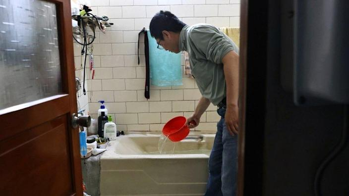 A man scoops water from a bathtub, where he stores water amid water rationing during an island-wide drought, in Hsinchu, Taiwan March 12, 2021.