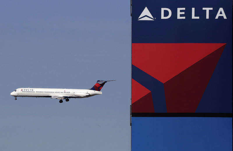 In this Saturday,  April 6, 2013, photo, a Delta Airlines jet flies past the company's billboard at Citi Field, in New York. Delta Air Lines Inc. reports quarterly financial results before the market opens Tuesday, April, 23, 2013. (AP Photo/Mark Lennihan)