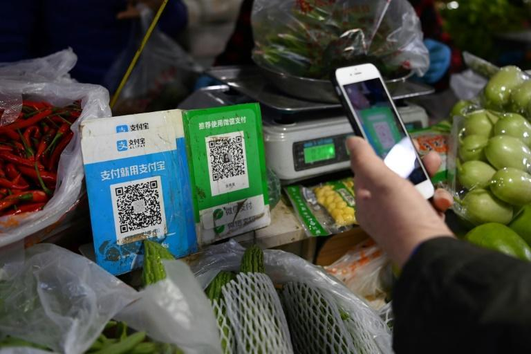 Alipay's app (QR code L) currently allows users to pay with a traditional credit card linked to their bank or offers small unsecured loans to buy anything from toilet paper to laptops (AFP/GREG BAKER)
