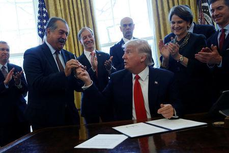 Dow Chemical CEO Andrew Liveris (L) reacts as U.S. President Donald Trump gives him the pen he used to sign an executive order on regulatory reform at his desk in the Oval Office at the White House, U.S. February 24, 2017. REUTERS/Jonathan Ernst
