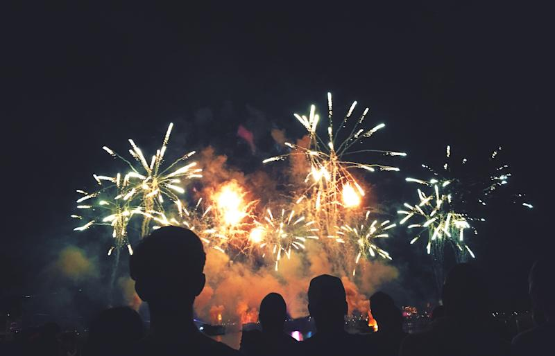 People in silhouette watch a fireworks display