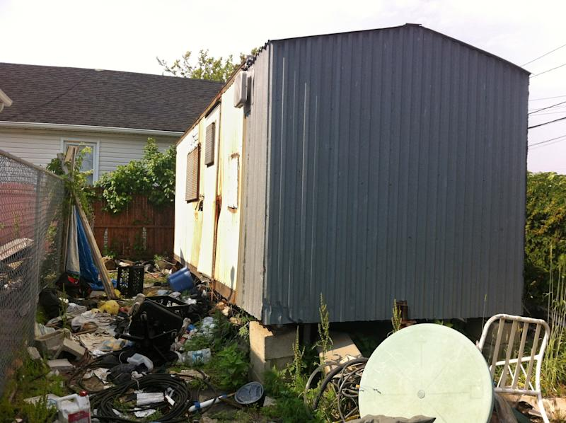A dilapidated trailer sits up on blocks in a trash strewn lot in the Queens borough of New York, Tuesday, June 15, 2013. Thought to be vacant, the trailer went unsearched after Superstorm Sandy flooded the area in late 2012. More than five month after the storm, the partially skeletonized remains of 62-year-old Keith Lancaster were found inside on April 5, 2013. He was among the 44 lives claimed by Sandy in New York City (AP Photo/Jake Pearson)