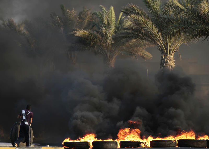 A masked Bahraini anti-government protester adds a tire to a row of others burning in a main street during clashes with riot police in Sitra, Bahrain, Monday, Sept. 3, 2012. Verdicts are expected Tuesday for numerous jailed leaders, medical workers and activists. (AP Photo/Hasan Jamali)
