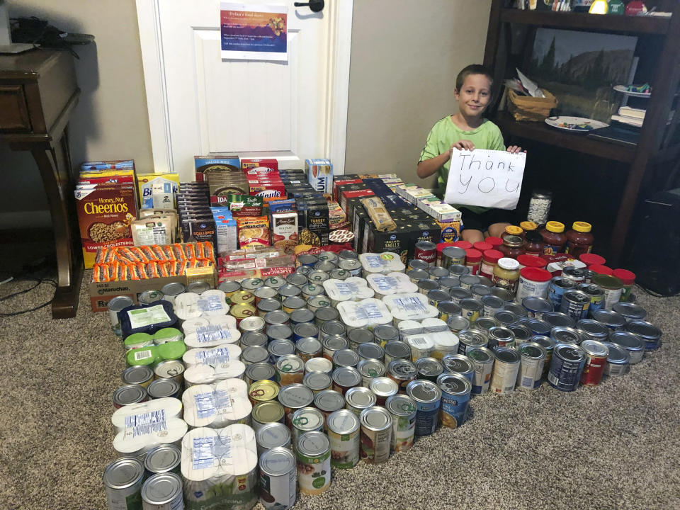 Dylan Pfeifer sits with all the donations he received during his first food drive at his home in Chandler, Ariz., in October 2020. Pfeifer received 316 cans and boxes of food. Each drive is the culmination of hours of work that involves drawing posters, going door-to-door to hand out flyers and working with his mother to post information on Facebook. (Erin Pfeifer via AP)