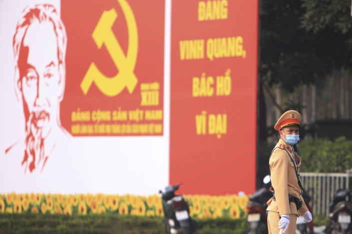 A police officer directs traffic in front of the National Convention Center in Hanoi, Vietnam, Saturday, Jan. 23, 2021. Almost 1,600 leading members of Vietnam's Communist Party on Tuesday, Jan. 26, 2021, begin a meeting to set policy for the next five years and select the group's senior members to steer the nation. (AP Photo/Hau Dinh)