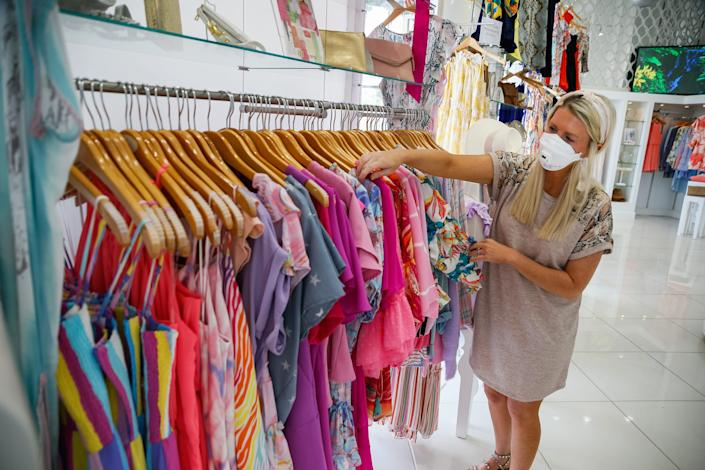 Emilee Young of Austin Lorin, a boutique in Colleyville, Texas, arranges tops as the store reopened on April 24.