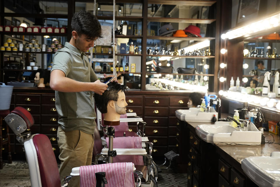 MANCHESTER, UNITED KINGDOM - JULY 02: Apprentice barber Sam Scott practices his scissor skills on a mannequin ahead of the Barber Barber salon opening by appointment on Saturday. July 02, 2020 in Manchester, United Kingdom. Many more retailers are reopening with social distancing measures after being shuttered for months due to the Covid-19 pandemic. Pubs and restaurants can fully reopen in England from July 4th. (Photo by Christopher Furlong/Getty Images)