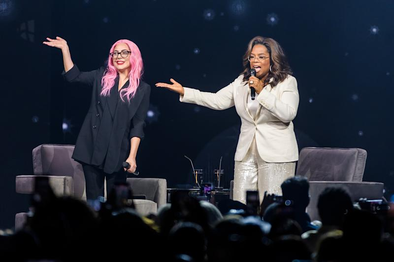 Lady Gaga waves at the crowd as she's onstage with Oprah