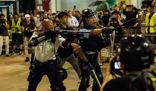 A police officer points a gun at protesters during clashes outside Kwai Chung Police Station. Photo: AFP