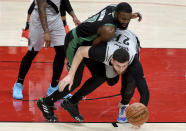 Boston Celtics guard Jaylen Brown, left, and Portland Trail Blazers center Jusuf Nurkic, right, go after a loose ball during the first half of an NBA basketball game in Portland, Ore., Tuesday, April 13, 2021. (AP Photo/Steve Dykes)