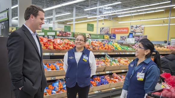 Walmart CEO Doug McMillon talking with two employees in the produce section of a Walmart store.