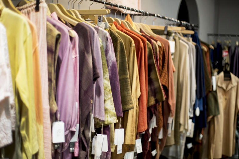 A hanging rail of women's clothing dyed using natural plant dyes, on a rail in a store.