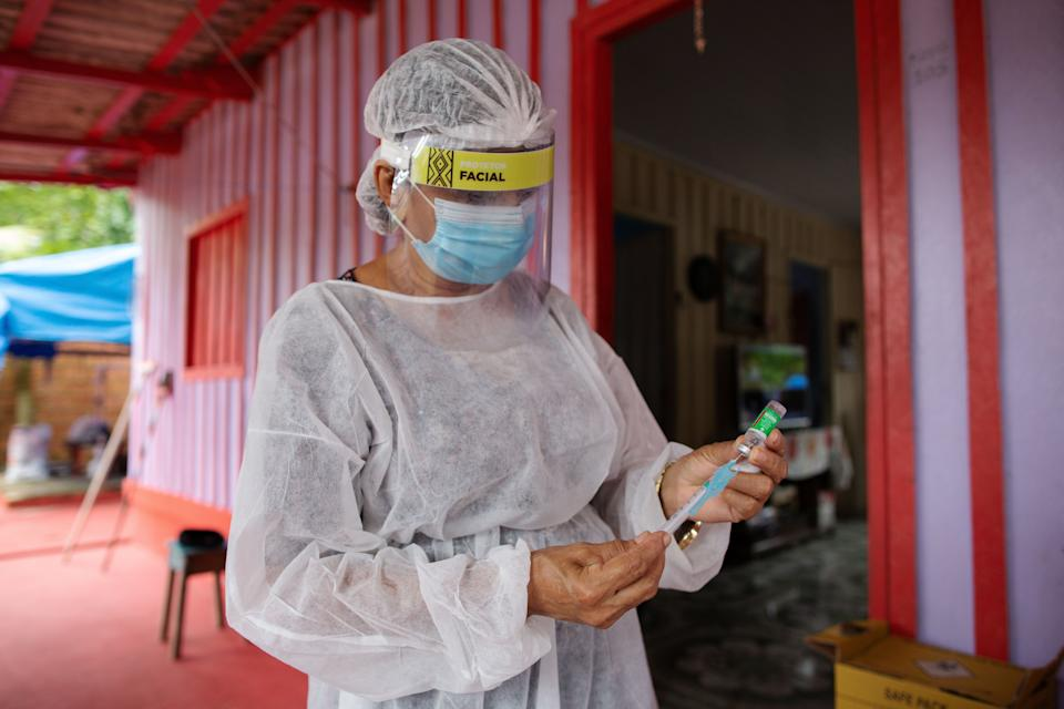 Nurse Janete Da Silva Oliveira prepares a dose of Oxford-AstraZeneca COVID-19 vaccine in the Nossa Senhora Livramento community on the banks of the Rio Negro near Manaus, Amazonas state, Brazil on February 9, 2021. (Photo by MICHAEL DANTAS / AFP) (Photo by MICHAEL DANTAS/AFP via Getty Images)