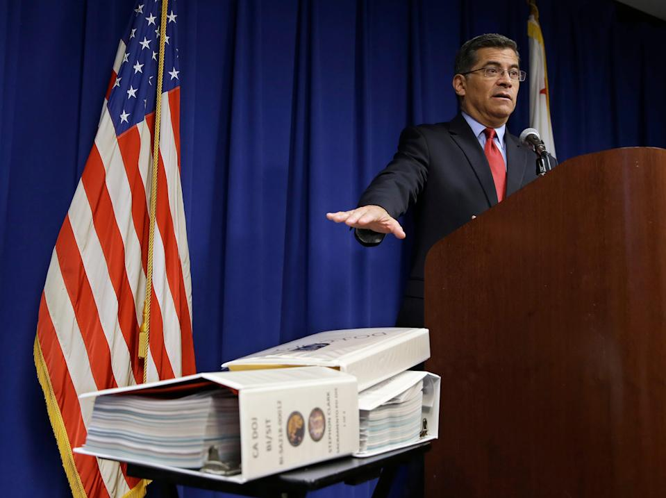 California Attorney General Xavier Becerra gestures towards the three binders containing his office's investigation into last year's fatal shooting of Stephon Clark by two Sacramento Police Officer, during a news conference,Tuesday, March 5, 2019, in Sacramento, Calif. Becerra said that after a nearly year long investigation, his office will not file criminal charges against the officers.