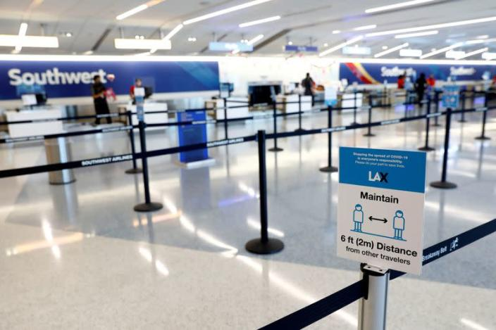 FILE PHOTO: Social distancing sign is displayed at a check-in area for Southwest Airlines Co. at Los Angeles International Airport (LAX) on an unusually empty Memorial Day weekend during the outbreak of the coronavirus disease (COVID-19) in Los Angeles