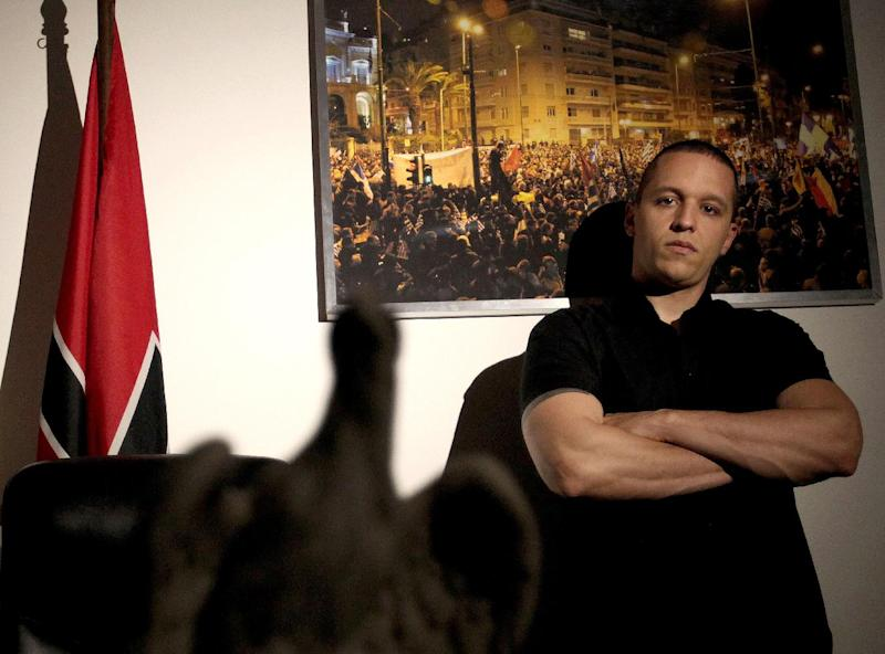 """In this picture taken on April 25, 2012 at the headquarters of the extreme far-right Golden Dawn party, Ilias Kasidiaris poses for a picture. The spokesman of the extreme-right Golden Dawn party, after trading insults of """"commie'' and ``fascist'' with two female left-wing politicians on a mainstream morning talk show, throwing water at one and smacking the other three times across the face. Prosecutors immediately issued an arrest warrant for Ilias Kasidiaris, whose party alarmed Europe by gaining 21 of Parliament's 300 seats in Greece's inconclusive May 6 elections. (AP Photo/Petros Giannakouris)"""