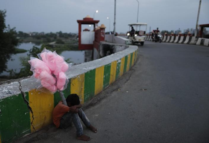 A young street vendor selling cotton candy lays his head on his knees sitting by a road