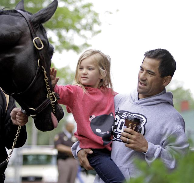Jockey Corey Nakatani shows his daughter Lilha Kentucky Derby hopeful Dance With Fate after a morning workout at Churchill Downs Wednesday, April 30, 2014, in Louisville, Ky. (AP Photo/Garry Jones)