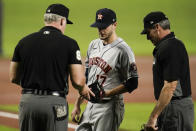 Houston Astros starting pitcher Jake Odorizzi (17) has his glove inspected by first base umpire Ted Barrett, left, and home plate umpire Angel Hernandez during the first inning of a baseball game against the Baltimore Orioles, Monday, June 21, 2021, in Baltimore. (AP Photo/Julio Cortez)