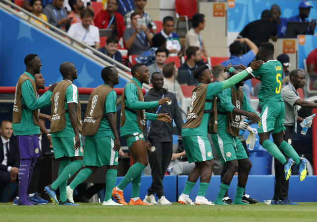 Senegal's Idrissa Gana Gueye, right, celebrates scoring his side's opening goal during the group H match between Poland and Senegal at the 2018 soccer World Cup in the Spartak Stadium in Moscow, Russia, Tuesday, June 19, 2018. (AP Photo/Eduardo Verdugo)