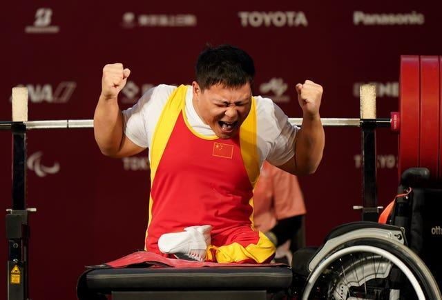 China's Yongkai Qi struggles to contain his delight after the third lift in the Men's -59 kg Final