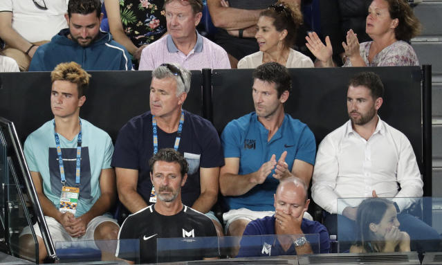 Serena Williams' coach, Patrick Mouratoglou, bottom left, sits in the player box of Greece's Stefanos Tsitsipas during his fourth round match against Switzerland's Roger Federer at the Australian Open tennis championships in Melbourne, Australia, Sunday, Jan. 20, 2019. (AP Photo/Aaron Favila)
