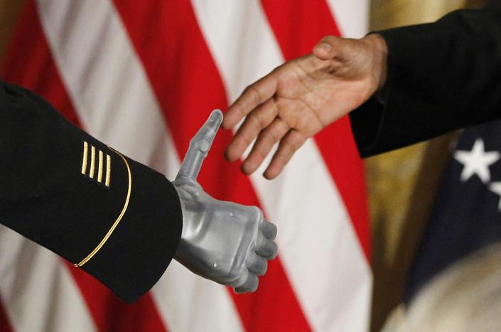 President Barack Obama shakes the prosthetic hand of U.S. Army Sgt. First Class Leroy Arthur Petry of Santa Fe, N.M., who received the Medal of Honor for his valor in Afghanistan in a ceremony in the East Room of the White House in Washington, Tuesday, July 12, 2011. Petry lost his right hand as he tossed aside a live grenade during a 2008 firefight in Afghanistan, sparing the lives of his fellow Army Rangers. (AP Photo/Charles Dharapak)