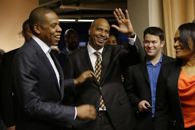 Rap artist Jay Z, one of the founders of Roc Nation Sports, stands with company president Juan Perez, center, as they are introduced at an event honoring Robinson Cano as the newest member of the Seattle Mariners baseball team, Thursday, Dec. 12, 2013, in Seattle. (AP Photo/Ted S. Warren)
