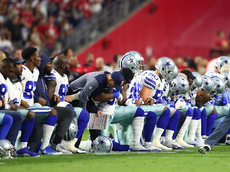 Sept. 25, 2017; Glendale, Ariz., Dallas Cowboys players kneel together with their arms locked prior to the game against the Arizona Cardinals at University of Phoenix Stadium.