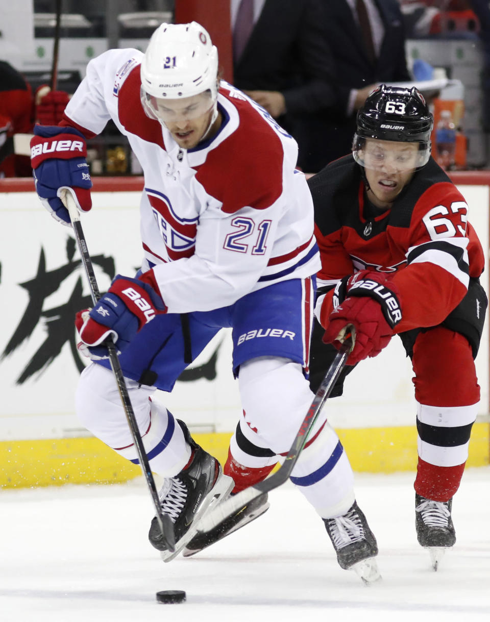New Jersey Devils left wing Jesper Bratt (63) gets his stick around Montreal Canadiens center Nick Cousins (21) during the first period of an NHL hockey game Tuesday, Feb. 4, 2020, in Newark, N.J. (AP Photo/Kathy Willens)