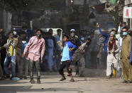 Supporters of Tehreek-e-Labiak Pakistan, a banned Islamist party, throw stones after police fire tear gas to disperse protests over the arrest of their party leader Saad Rizvi, in Karachi, Pakistan, Monday, April 19, 2021. The outlawed Islamist political group freed 11 policemen almost a day after taking them hostage in the eastern city of Lahore amid violent clashes with security forces, the country's interior minister said Monday. (AP Photo/Fareed Khan)
