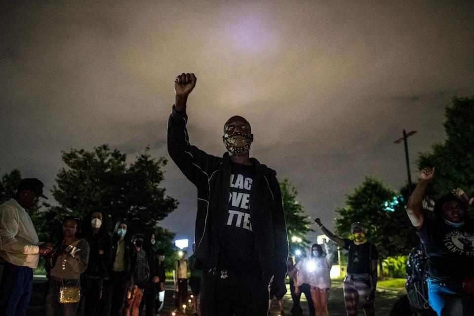 A protester raises his hand as he protests outside a burned Wendy's restaurant on the third day following Rayshard Brooks shooting death by police in the restaurant parking lot in Atlanta, Georgia, June 15, 2020. (Chandan Khanna/AFP via Getty Images)