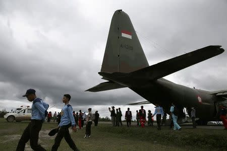Search and Rescue team members walk near a Hercules C-130, as they wait for better weather conditions to take off for their search operation for the AirAsia flight QZ8501, at Iskandar airbase in Pangkalan Bun district, Indonesia, December 31, 2014. REUTERS/Beawiharta