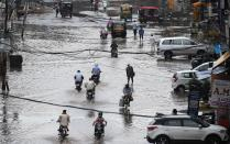 Commuters make their way along a water-logged street following heavy rains in Amritsar on July 19, 2020. (Photo by NARINDER NANU / AFP) (Photo by NARINDER NANU/AFP via Getty Images)