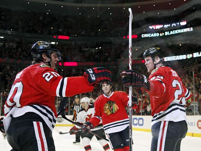 Chicago Blackhawks left wing Bryan Bickell, right, celebrates his goal with left wing Brandon Saad (20) and Andrew Shaw during the second period of an NHL hockey game against the New Jersey Devils, Monday, Dec. 23, 2013, in Chicago. (AP Photo/Charles Rex Arbogast)