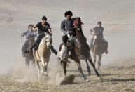 Young horse riders compete for the goat during a kok boru, also called ulak tartysh a traditional game in which players on horseback maneuver with a goat's carcass and score by putting it into the opponents' goal outside Tash Bashat village, about 24 kilometers (15 miles) southeast of Bishkek, Kyrgyzstan, Saturday, Oct. 17, 2020. The political turmoil that has gripped Kyrgyzstan hasn't reached this quiet village in the mountains near the capital, where residents talk about the country's feuding elites with resignation and disdain.(AP Photo/Vladimir Voronin)