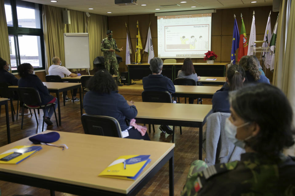 Army Sgt. Ari Silva, background left, gives a talk on COVID-19 safety procedures to a care home staff in Amadora, outside Lisbon, Friday, Dec. 11, 2020. As a resurgence of the pandemic in the fall looked set to overwhelm Portuguese care homes, and the country's public health service struggled to cope, the government mobilized all the resources it could. That included deploying military units. (AP Photo/Armando Franca)