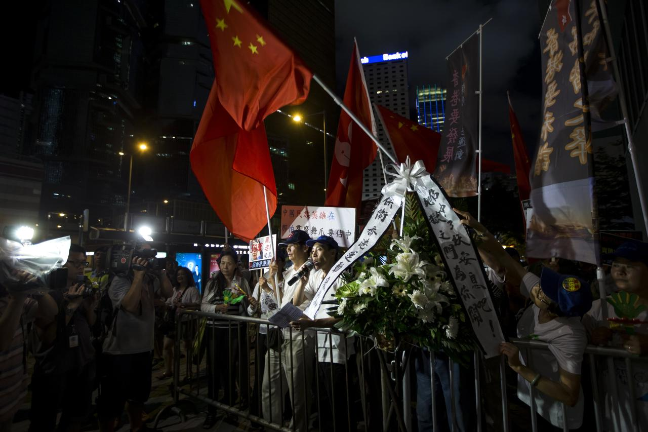 Pro-Beijing protesters take part in a rally with Chinese national flag to support Beijing in exercising decisive action outside the Chief Executive's Office in Hong Kong August 31, 2014. China's parliament said on Sunday it will tightly control the nomination of candidates for a landmark election in Hong Kong in 2017, a move likely to trigger mass protests in the city's Central business district by disappointed democracy activists. REUTERS/Tyrone Siu (CHINA - Tags: POLITICS)