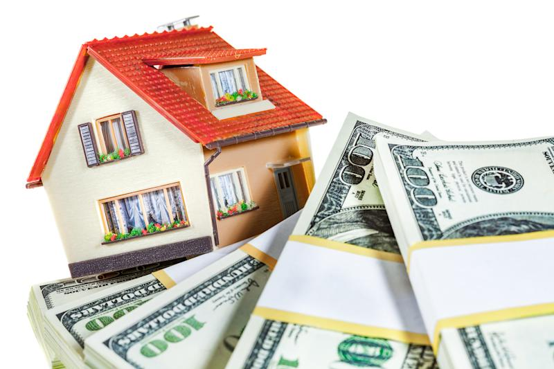 A toy house sitting atop bundles of hundred-dollar bills.
