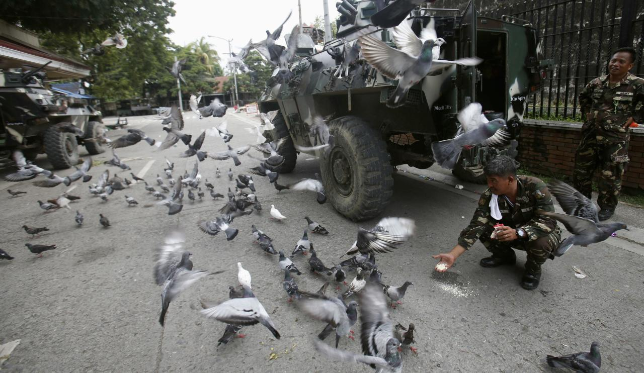 Government soldiers of Task Force Zamboanga (TFZ) feed pigeons with bread crumbs near a military command post during a lull in fighting with Muslim rebels of Moro National Liberation Front (MNLF), in Zamboanga city in southern Philippines September 16, 2013. REUTERS/Erik De Castro (PHILIPPINES - Tags: CIVIL UNREST CONFLICT POLITICS MILITARY ANIMALS)