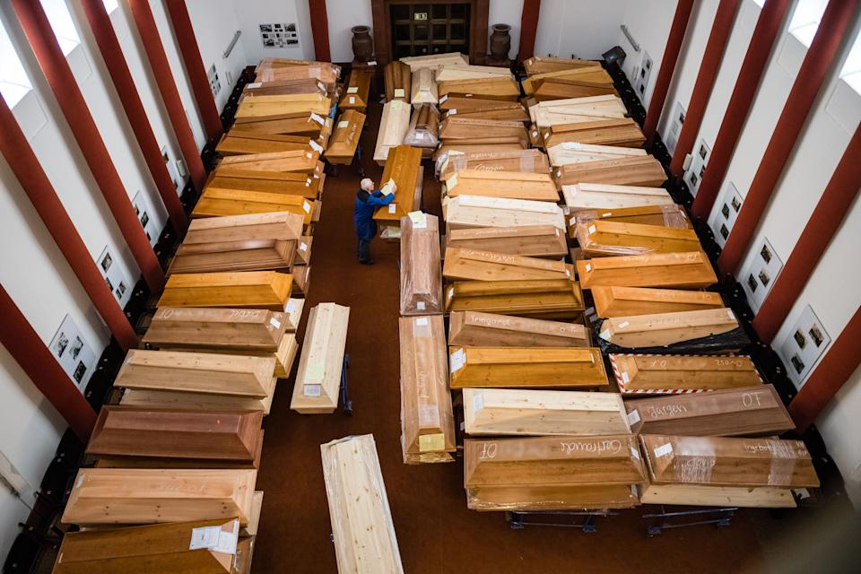 TOPSHOT - An employee stores coffins among many others in the mourning hall of the crematorium in Meissen, eastern Germany, on January 13, 2021. - Most of the deceased, who will be cremated here, have died of or with the coronavirus. (Photo by JENS SCHLUETER / AFP) / EDITORS NOTE: the family names written on the coffins have been blurred (Photo by JENS SCHLUETER/AFP via Getty Images) (Photo: JENS SCHLUETER via Getty Images)