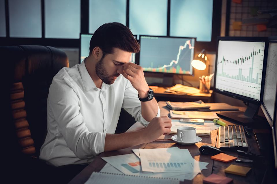 Depressed frustrated trader tired of overwork or stressed by bankruptcy, sad shocked investor desperate about financial crisis or money loss, upset businessman having headache massaging nose bridge