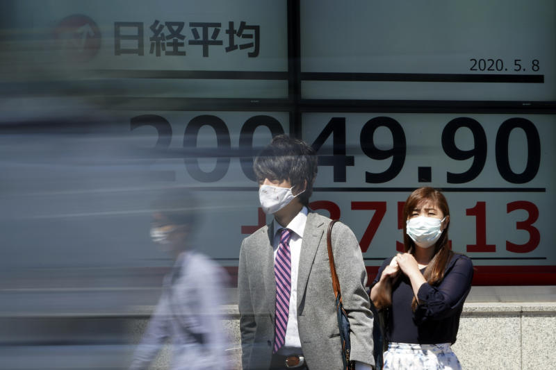 People wearing a face mask to help curb the spread of the coronavirus stand near an electronic stock board showing Japan's Nikkei 225 index at a securities firm in Tokyo Friday, May 8, 2020. Asian shares surged Friday on optimism the worst of the economic fallout from the pandemic may be over, as Wall Street logged its biggest rally in a week.(AP Photo/Eugene Hoshiko)